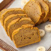 pumpkin banana bread sliced on a pan with bananas